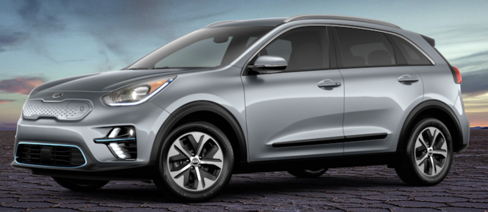 Side view of 2019 Kia Niro electric car in aluminum silver color against a sky at dusk.