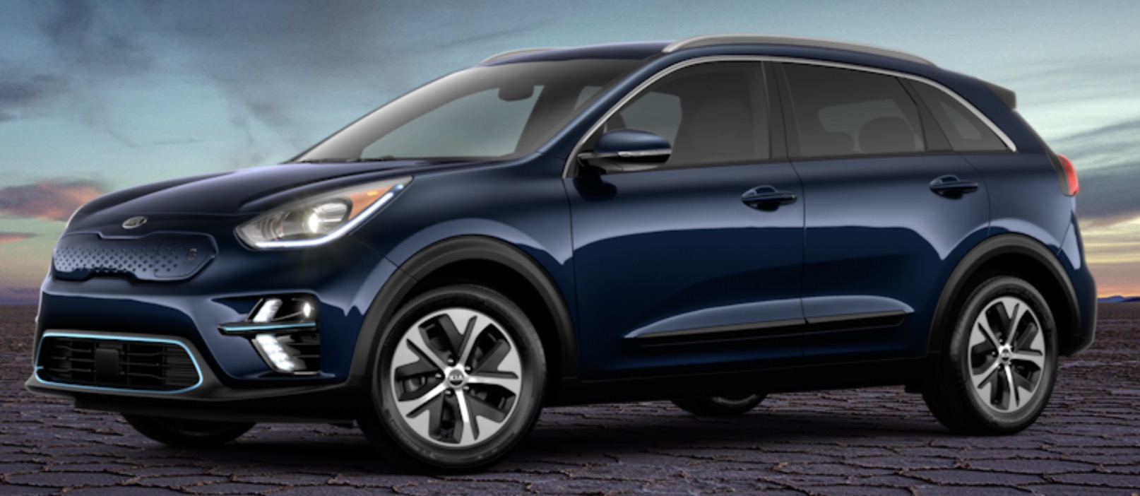 Side view of 2019 Kia Niro electric car in gravity blue color against a sky at dusk.