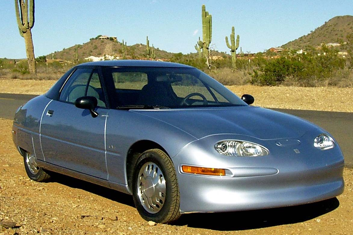 GM's 1996 EV1, parked roadside in the desert, pivotal as first electric vehicle mass-produced by a major manufacturer.