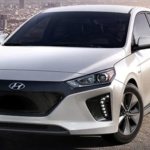 Front-angled view of 2019 Hyundai Ioniq electric car in ceramic white color set against city skyline.