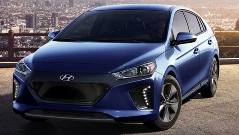 Front-angled view of 2019 Hyundai Ioniq electric car in intense blue color set against city skyline.