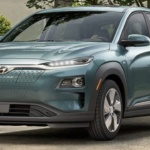 Front-angled view of 2019 Hyundai Kona electric car in ceramic blue color parked in a leafy driveway.