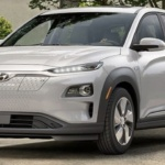 Front-angled view of 2019 Hyundai Kona electric car in chalk white color parked in a leafy driveway.