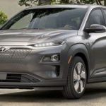 Front-angled view of 2019 Hyundai Kona electric car in galactic grey color parked in a leafy driveway.