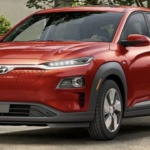Front-angled view of 2019 Hyundai Kona electric car in pulse red color parked in a leafy driveway.