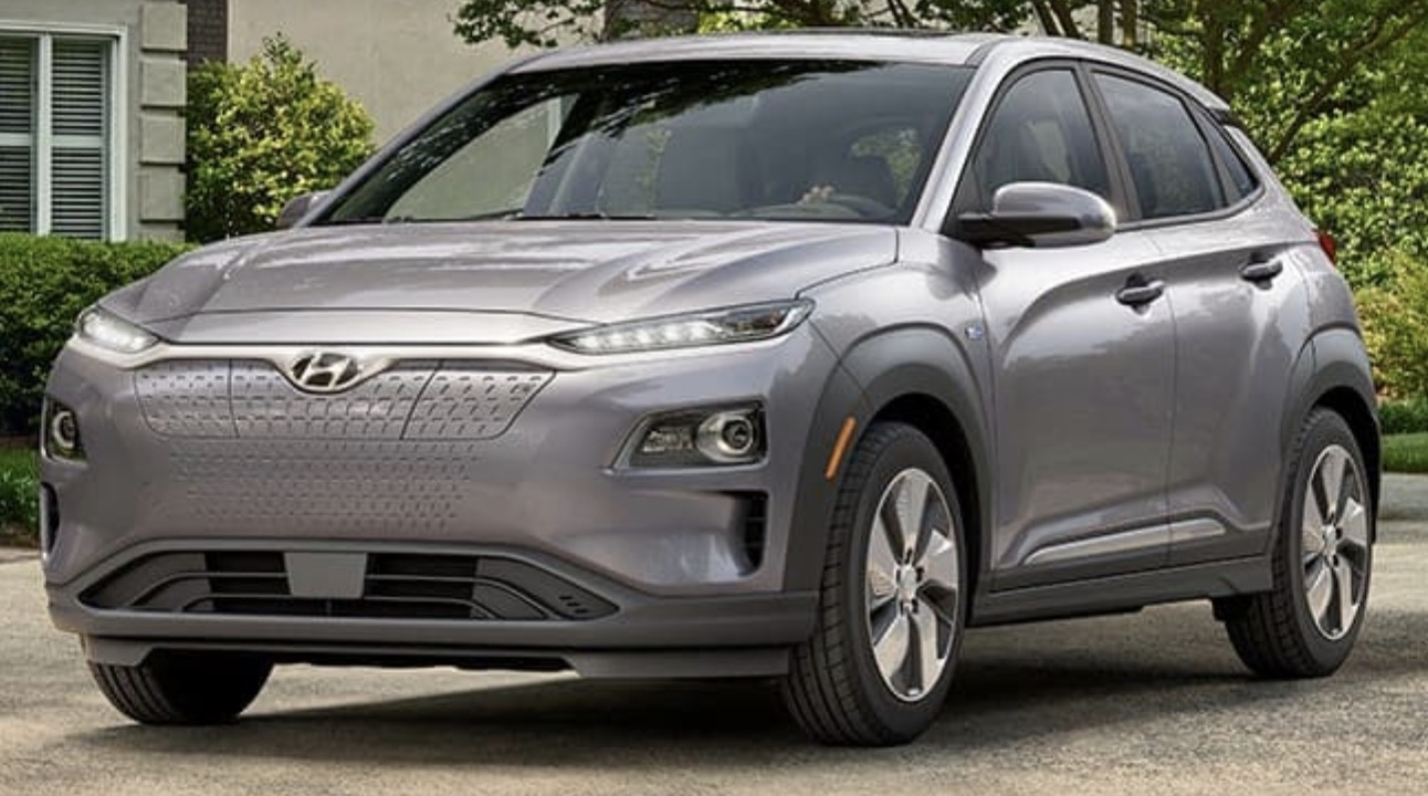Front-angled view of 2019 Hyundai Kona electric car in sonic silver color parked in a leafy driveway.