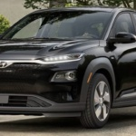 Front-angled view of 2019 Hyundai Kona electric car in ultra black parked in leafy driveway.