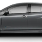 Side-view of 2019 Nissan Leaf electric car in gun metallic gray against a white background.