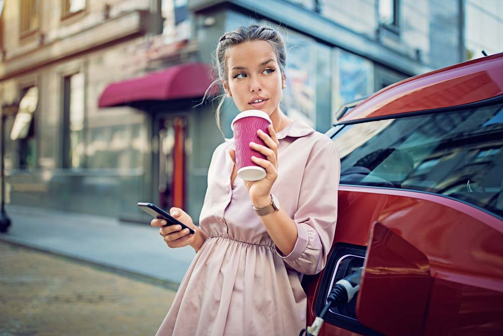 Young woman texting while waiting for her electric car to charge.